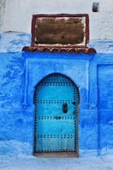 Ancient blue door in Chefchaouen medina in Morocco.
