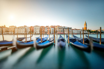 Obraz Venice cityscape view on Grand canal with colorful buildings, gondolas and San Marco campanille at the sunset. Long exposure image technic with motion blurred boats and glossy water - fototapety do salonu