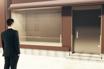 Confident businessman looking at storefront
