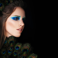 Glamorous Woman with Makeup and Peacock Feathers on Black Backgr
