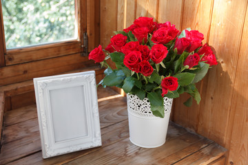 White frame and bunch of red roses