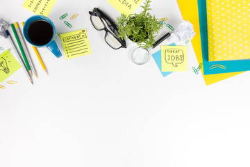 Office table desk with green supplies, blank note pad, cup, pen, glasses, crumpled paper, magnifying glass, flower on white background. Top view
