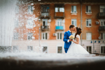 Bride and groom near the fountain in the summer