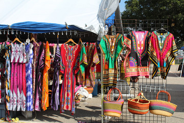 Brightly colored African fashions displayed at an outdoor flea market