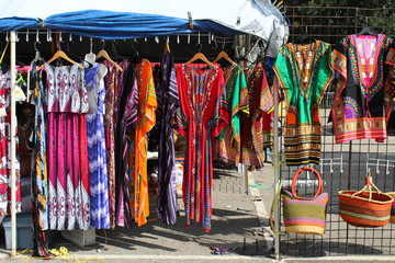 Colorful African dashikis, dresses, and woven bags at an outdoor flea market