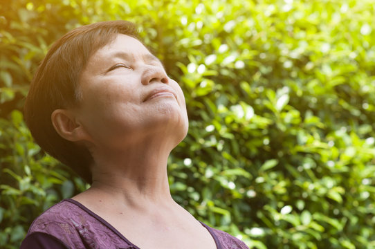Asian senior woman relaxing and breathing fresh air.