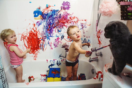 Portrait of two cute adorable white Caucasian little boy and girl playing painting cat with paints in bathroom having fun, lifestyle childhood concept