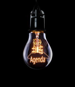 Hanging lightbulb with glowing Agenda concept.
