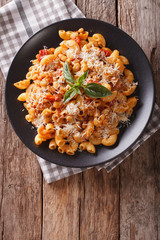 gomiti pasta with white beans and cheese on a plate close-up. Vertical top view