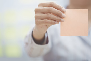 Hand of woman holding sticky note with empty space