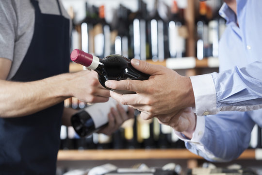 Midsection Of Customer And Salesman With Wine Bottles