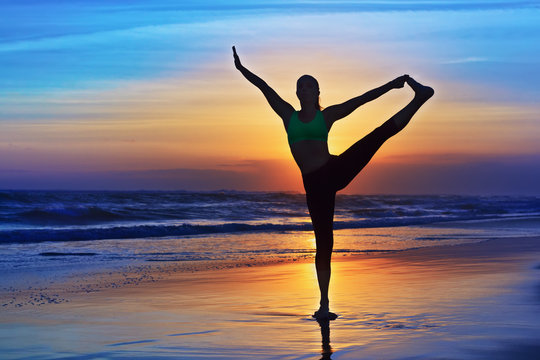 Black silhouette of woman stretching at yoga retreat on sunset sand beach, colourful sky, ocean surf background. Lifestyles, people outdoor activity, sport on family summer vacation on tropical island