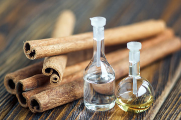 Essential oil in glass bottle with cinnamon sticks on wooden background. Beauty treatment. Spa concept. Selective focus.