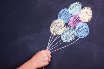 hand holding chalk drawing balloons