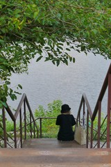 lonely woman in black hat on a stairs