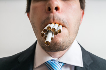 Young man has full mouth of cigarettes. He wants to smoke many cigarettes at once.