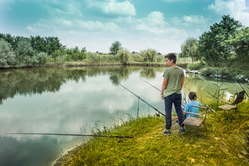 Father and sons fishing on river