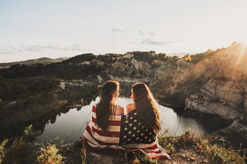 Back view of girlfriends in american flag sitting on edge against of lake