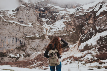 Brunette traveler with backpack on winter landscape