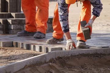 Bricklayer places concrete paving stone blocks