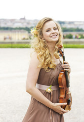 Beautiful smiling girl with a violin outdoor.Beautiful smiling girl playing on the violin outdoors. Musician for the wedding.Violin under the open sky
