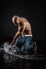 athletic man striking with a hand on water