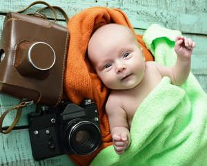 Portrait of cute baby boy with retro photo cameras