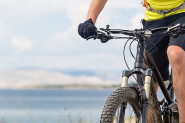 Mountain biker riding on bike at the sea and summer mountains. Sport and training outdoors.