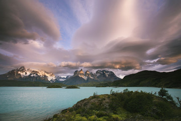 Cloud formations in the skies above the Torres del Paine National Park in Chile. Sunset over the waters of the sea, and snow-capped peaks.