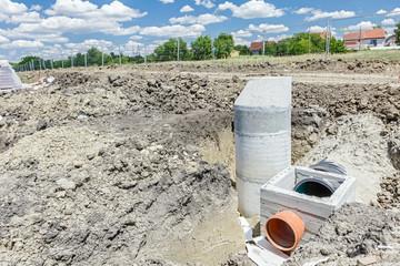 Concrete drainage manhole is unfinished on building site.
