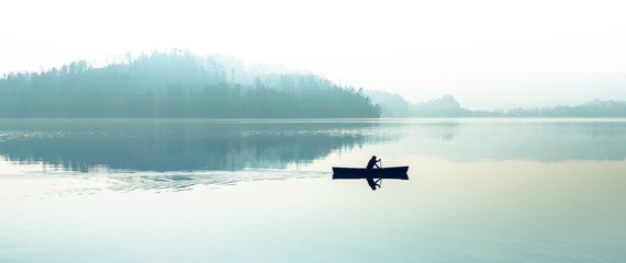Fog over the lake. Silhouette of mountains in the background. The man floats in a boat with a paddle. Fototapete
