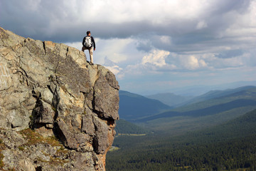 Hiker with backpack standing on top off high rocks. Tourism conc