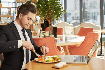 Starving mind. Handsome suited businessman having lunch while working on his laptop at the restaurant