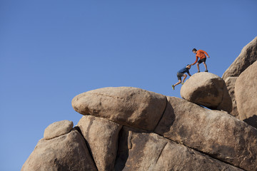Two men playing around on giant boulders.