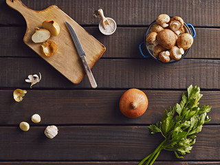 Fresh onion, garlic and mushrooms on the wooden background, prepared for cooking. Top view.