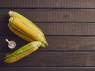 Fresh sweet corn on wooden table. Top view. Free copy space.