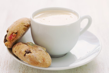 cup of coffee with cookies on wooden background