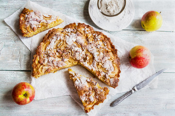 Sliced homemade apple and almond cake on wooden background. Fresh fruits and icing sugar, top view