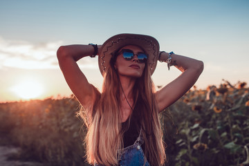 Girl in a cowboy hat in a sunflower field. Sunset