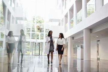 Female Doctors Talking As They Walk Through Hospital