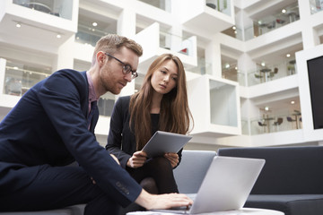 Two Businesspeople Using Laptop In Lobby Of Modern Office