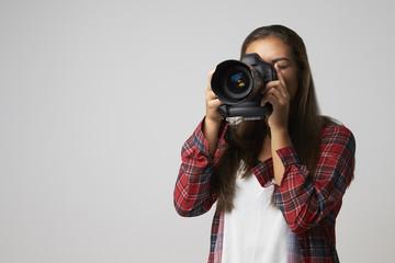 Studio Portrait Of Female Photographer With Camera