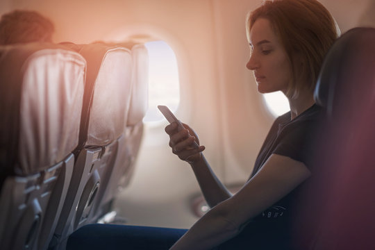 Portrait young woman using modern smartphone at plane, Woman working at plane, businesswoman working at airplane, blurred background, shallow DOF.