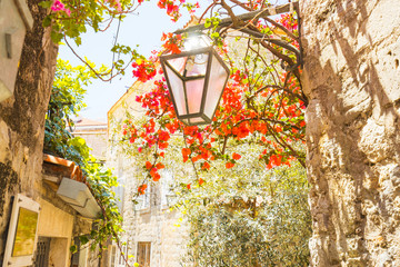 Street light and flowers. Narrow streets of the old town of Budva, Montenegro.