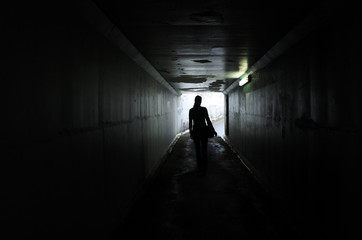 Silhouette of a young woman walks alone in a dark tunnel Wall mural