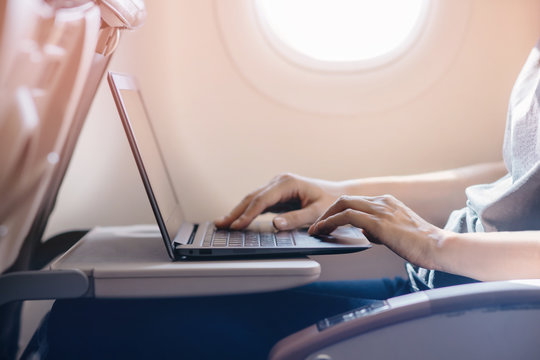 Woman typing text on laptop, young girl using modern laptop at airplane, blurred background, shallow DOF.