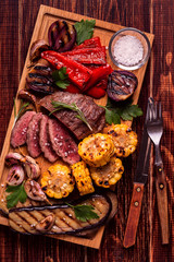 Grilled steak and vegetables on cutting board.