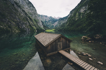 Wood cabin and mountains reflected in water