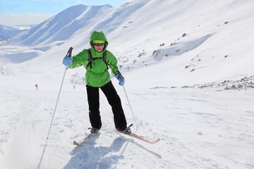 Young woman rises in the snowy slopes on skis in Hibiny mountains.