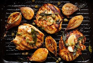Grilled turkey fillet steak with addition herbs and shallot onions on the grill pan, top view